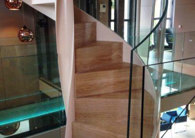 Escalera helicodal con huella y contrahuella en madera  y  barandilla de vidrio. -Cris-